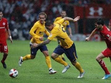Fernando Torres intenta avanzar con el balón ante la mirada de Griezmann