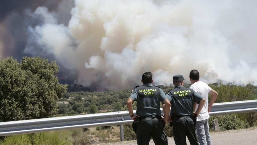 Agentes de la Guardia Civil observan el incendio forestal declarado en la Nacional 122