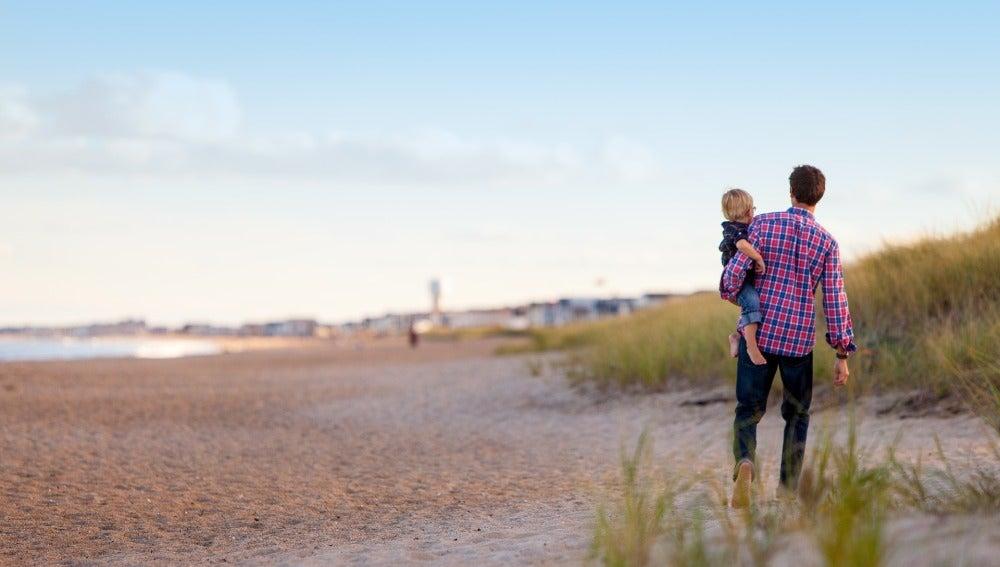 Padre caminado por la playa con su hijo