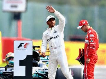 Lewis Hamilton saluda al público con Vettel cabizbajo al fondo