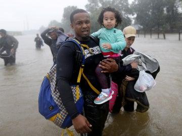 Padre e hija huyendo de las inundaciones provocadas por Harvey