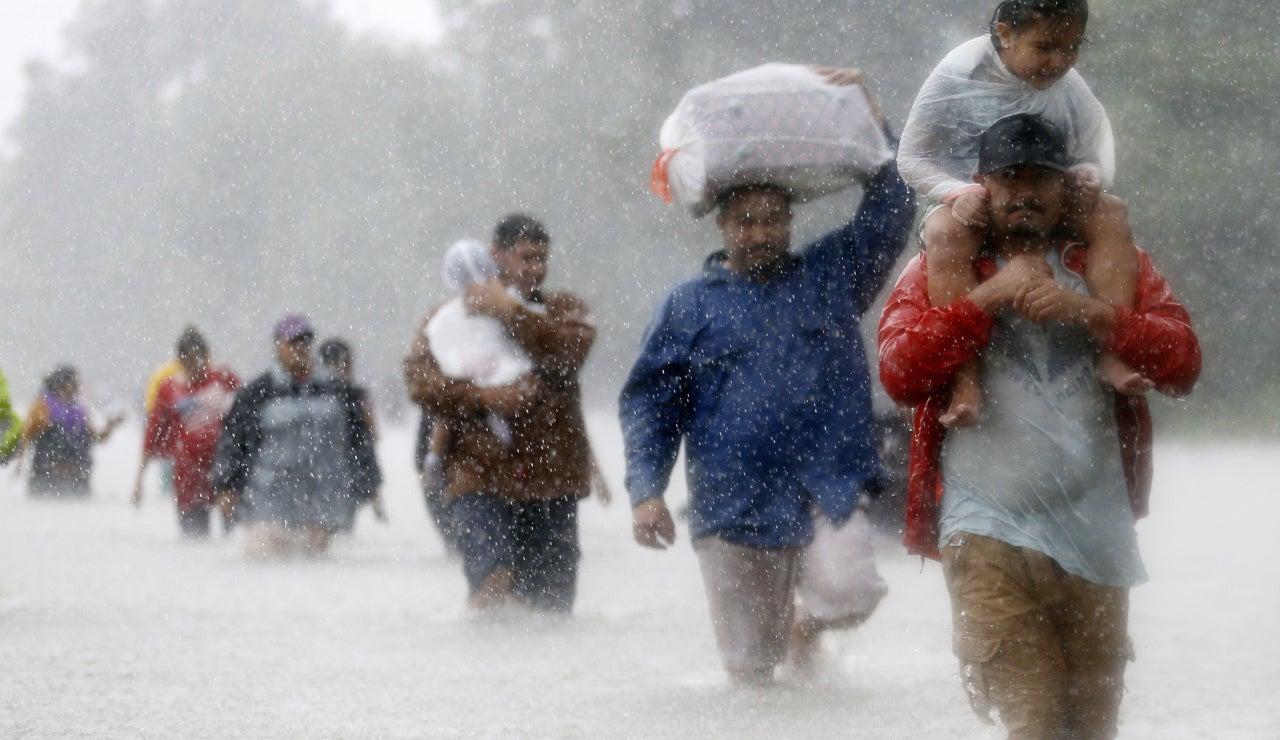Los residentes, por las zonas inundadas que deja la tormenta tropical Harvey en Beaumont Place, Houston