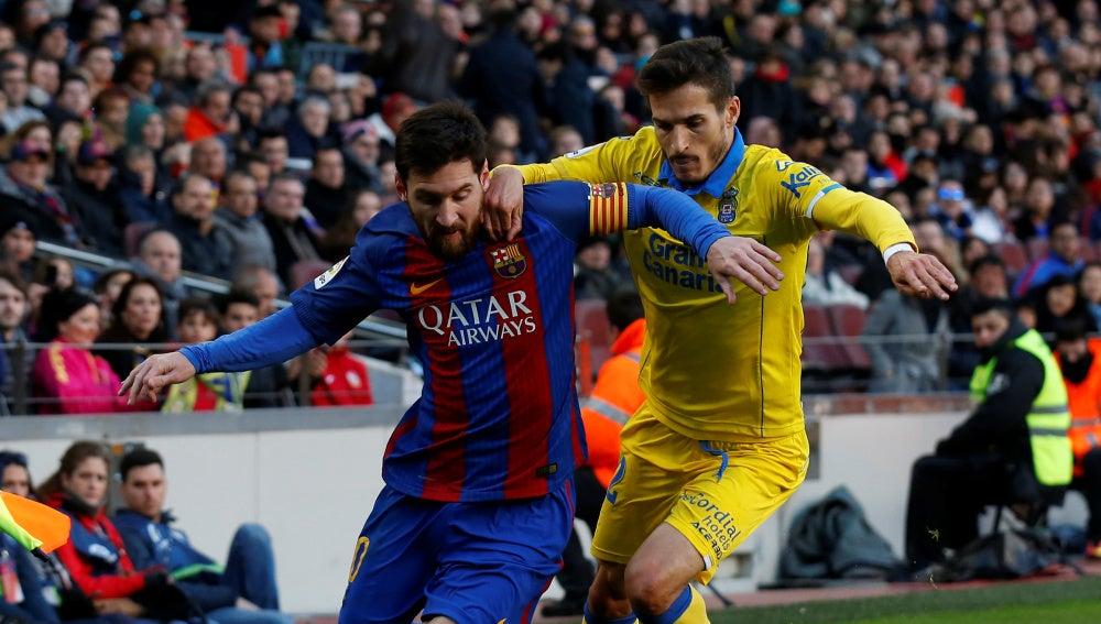 Leo Messi intenta zafarse de Helder Lopes en un Barcelona - Las Palmas