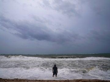 Imagen de archivo de un hombre en una playa con el cielo nuboso