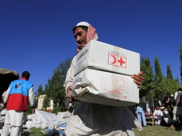 Afgano con cajas de ayuda de la Cruz Roja