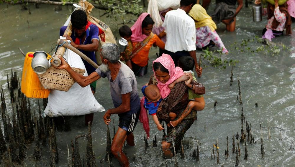 Refugiados Rohingya caminan a través del agua después de cruzar la frontera en barco a través del río Naf en Teknaf en Bangladesh