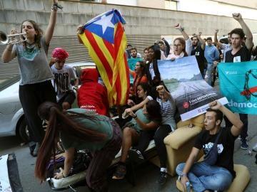Numerosas personas protestan ante la oficina de la empresa de mensajería Unipost en Terrassa