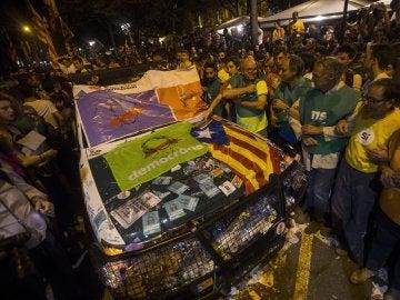 Un coche de la Guardia Civil destrozada frente a la Consellería de Economía