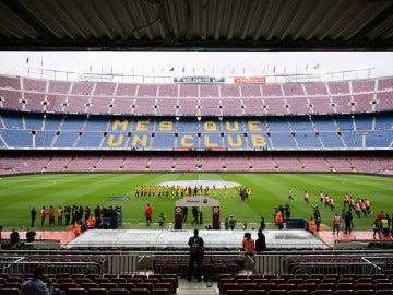 Los jugadores se chocan la mano en un Camp Nou completamente vacío