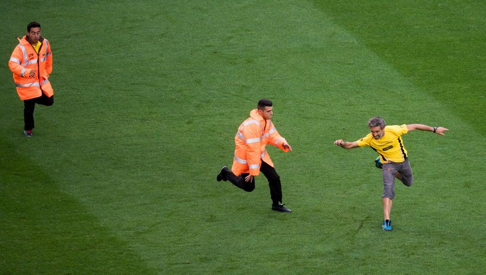Un aficionado sortea el placaje de un miembro de seguridad en el partido del Barça a puerta cerrada