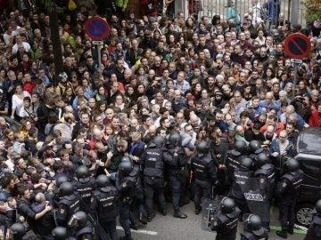 Antidisturbios de la Policía Nacional forman un cordón de seguridad en los alrededores del colegio Ramón Llull de Barcelona