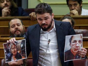 El portavoz de ERC, Gabriel Rufián, muestra unas fotografías durante su intervención