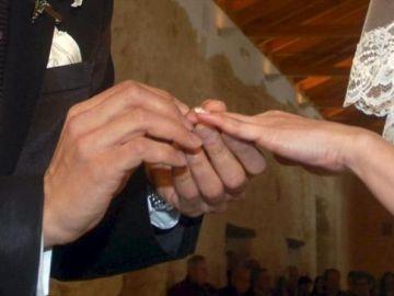 Manos de una pareja intercambiando los anillos en la ceremonia de su boda