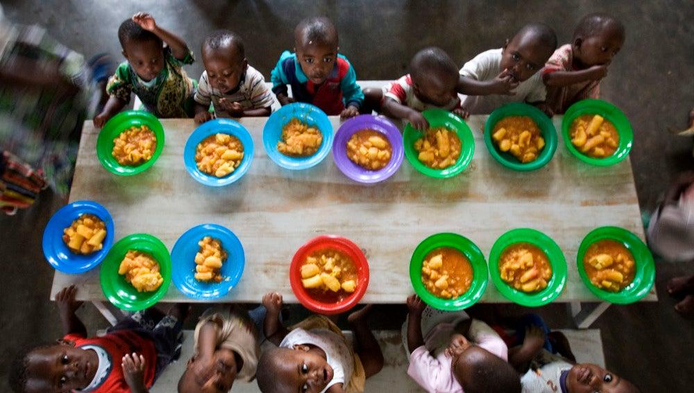 Varios niños huérfanos cenan en un orfanato