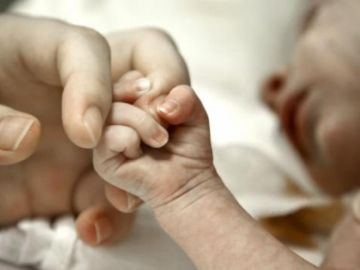 Un bebe coge de la mano a su madre