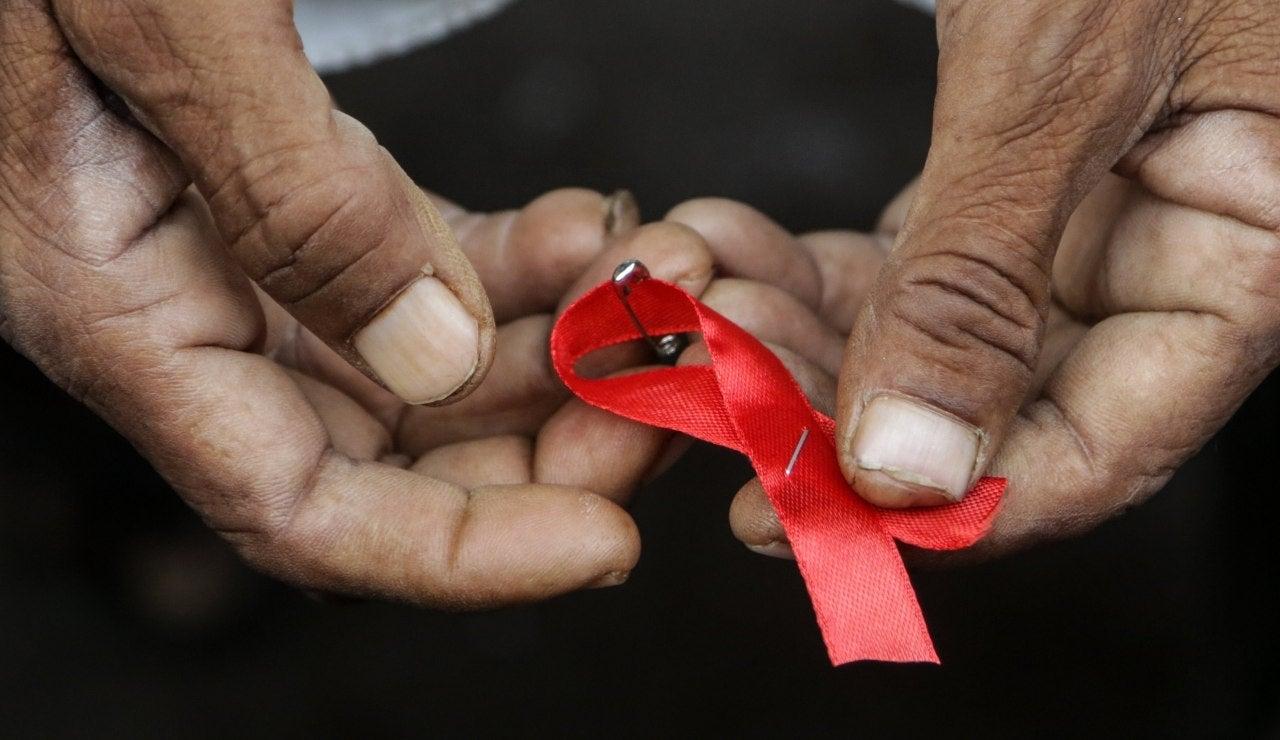 Un hombre sostiene el lazo rojo que conmemora el Día Mundial de la Lucha contra el Sida