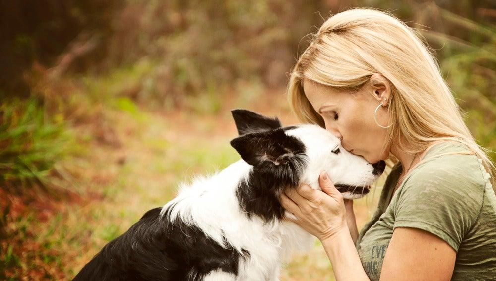 Una mujer dándole un beso a su perro