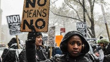 Una mujer sujeta un cartel en contra del acoso sexual fuera del Trump International Hotel