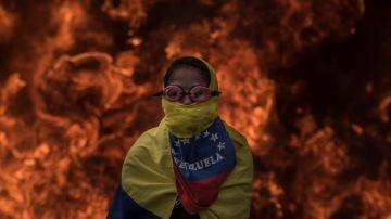Una activista de la oposición venezolana se cubre la cara frente al fuego de la barricadas