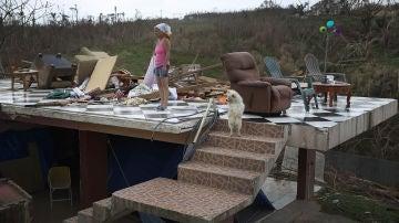 Irma Maldanado, junto con su loro y su perro, en lo que queda de su casa tras el paso del huracán María
