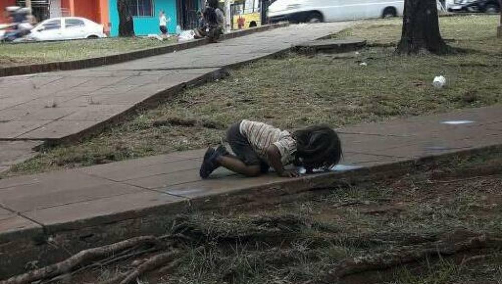 Una niña bebiendo de un charco