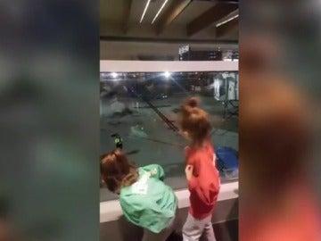 El divertido baile de dos niñas en el aeropuerto que siguen el ritmo que les marca un trabajador desde la pista