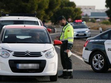 Un agente de la Guardia Civil da el alto a un vehículo en un control de tráfico