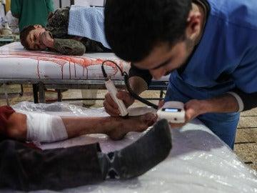 Un médico atiende a una víctima de un bombardeo en Siria