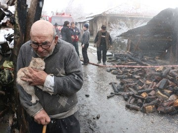 Un anciano abraza a su gato tras el incendio de su casa