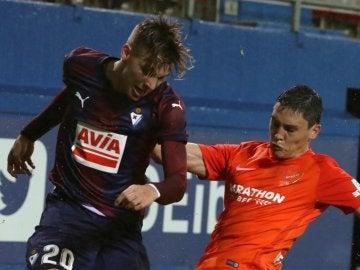 Ricca e Iván Alejo luchan por la posesión del esférico durante el Eibar - Málaga