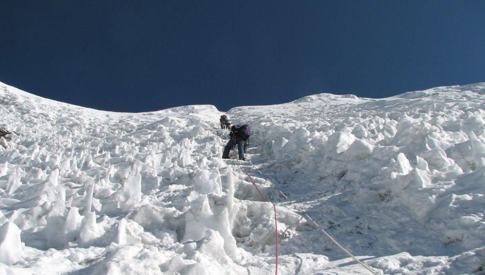 Unos montañeros escalando en la nieve