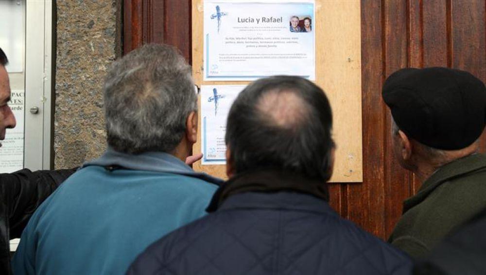 Vecinos de los fallecidos, observan la esquela de los dos ancianos encontrados muertos con signos de violencia