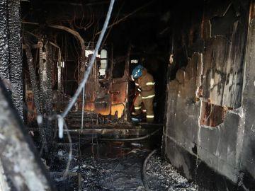 Bomberos apagan los restos del fuego en un cuarto de hospital Sejong