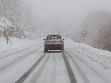Un vehículo circula por una carretera nevada