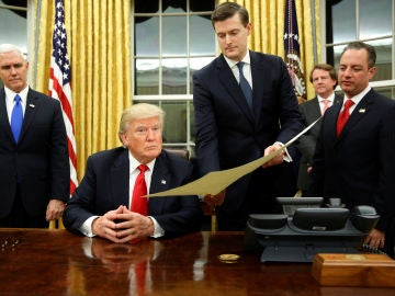Rob Porter, secretario personal de la Casa Blanca, sujeta un documento a Donald Trump
