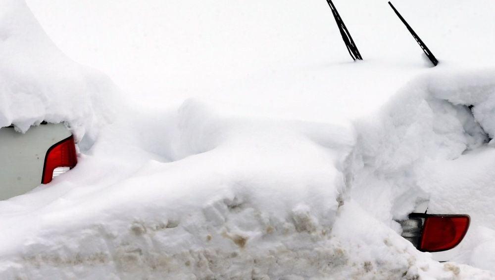 Dos vehículos cubiertos por nieve