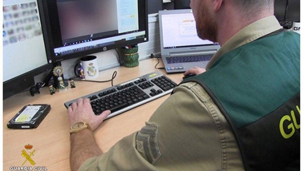 Un agente de la Guardia Civil analizan las fotografías que tenía el depredador sexual detenido
