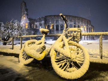 Una bicicleta cubierta de nieve con el Coliseo de Roma al fondo