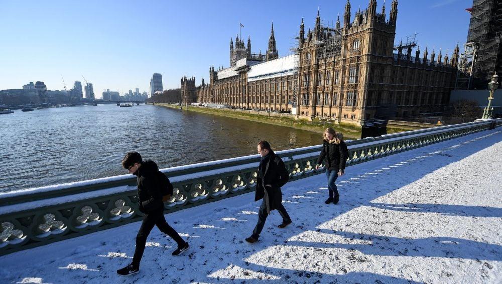 Varios viandantes caminan por la nieve sobre el Puente de Westminster