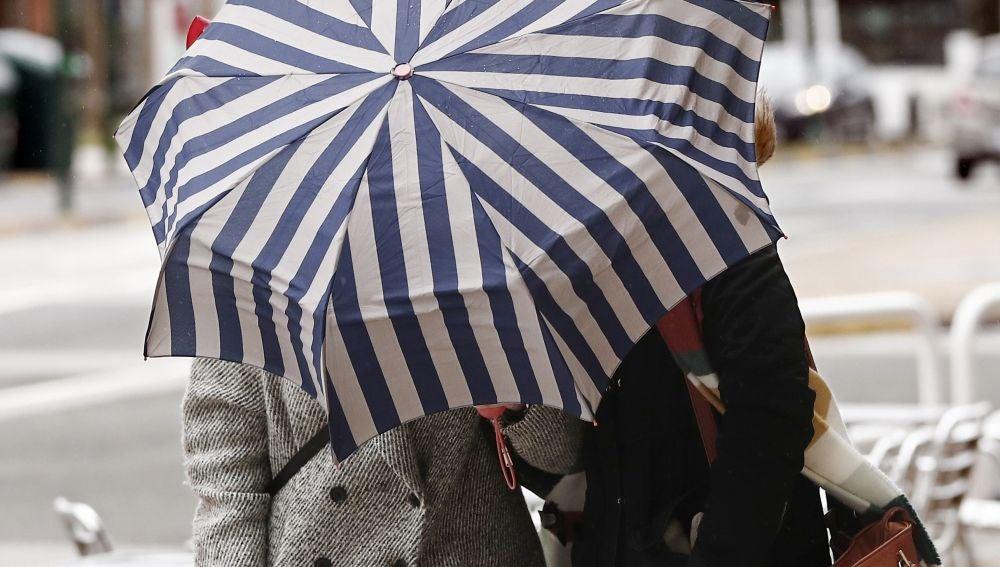Dos mujeres se protegen con un paragüas de la lluvia y el viento en Pamplona