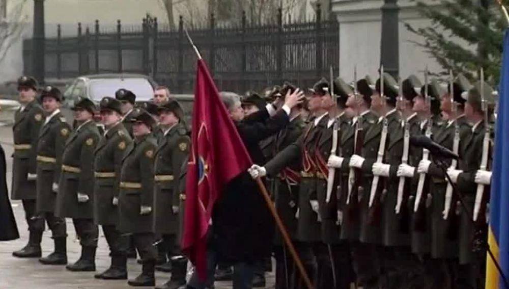 El presidente de Ucrania coloca el gorro a un soldado