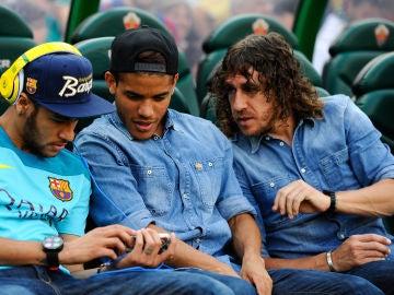 Neymar enseña su móvil a Jonathan dos Santos y a Puyol