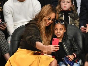 Beyoncé y Blue Ivy haciéndose un selfie durante un partido de la NBA