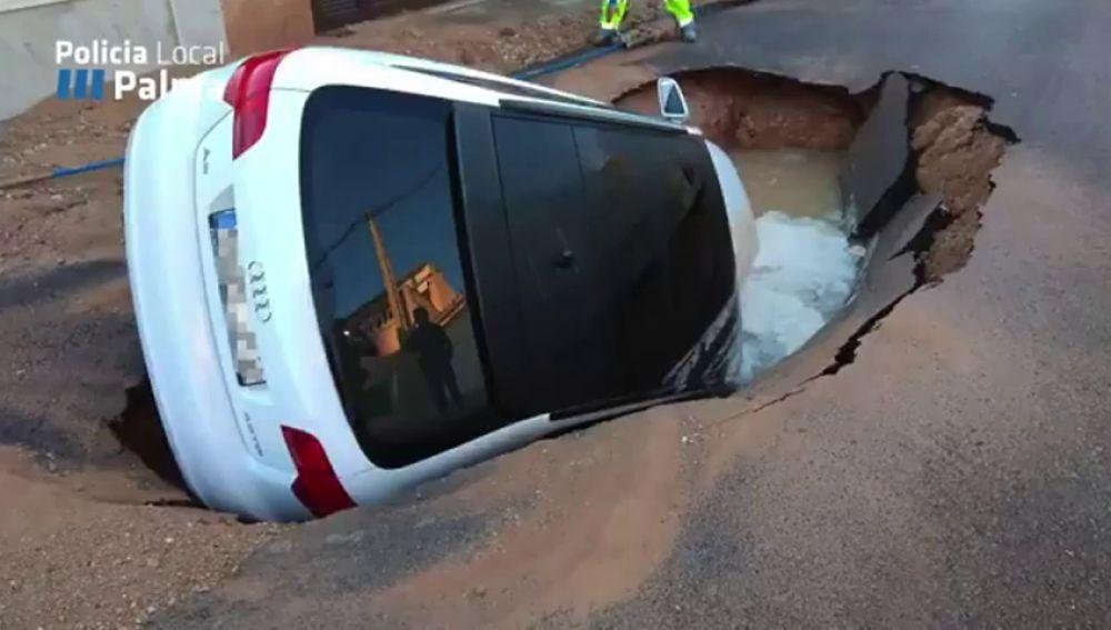 Una fuga de agua provoca un socavón y engulle un coche