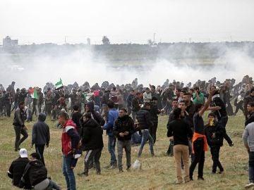 Palestinos huyen de gases lacrimógenos durante los enfrentamientos con soldados israelíes