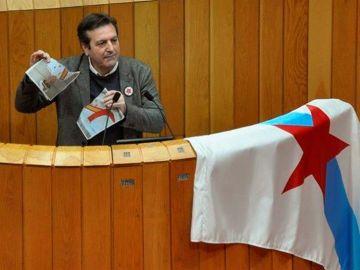 El diputado del BNG, Luís Bará, rompiendo una foto del Rey