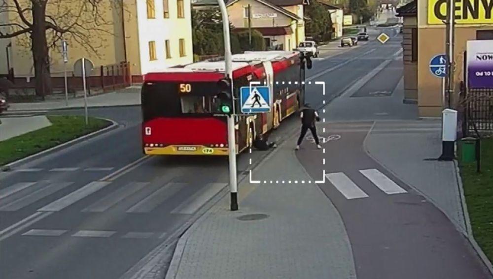 Una joven cae a la carretera justo cuando el autobús pasaba