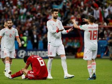 Piqué se saluda a Jordi Alba durante el partido contra Irán