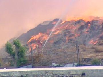 Bomberos trabajan en la extinción de un incendio en una fábrica abandonada de madera en la localidad valenciana de Sollana
