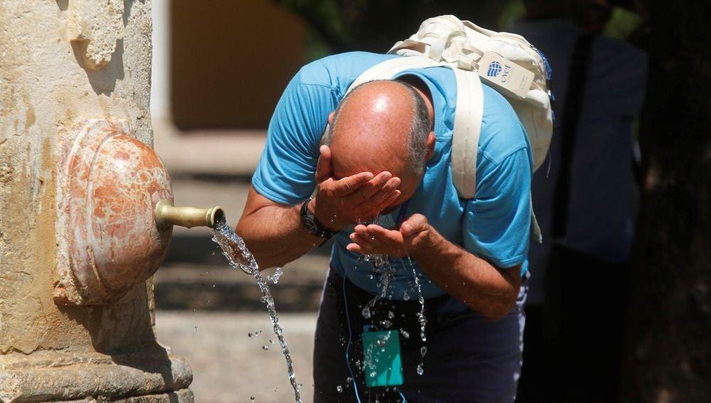 Un hombre se refrescaba en una fuente
